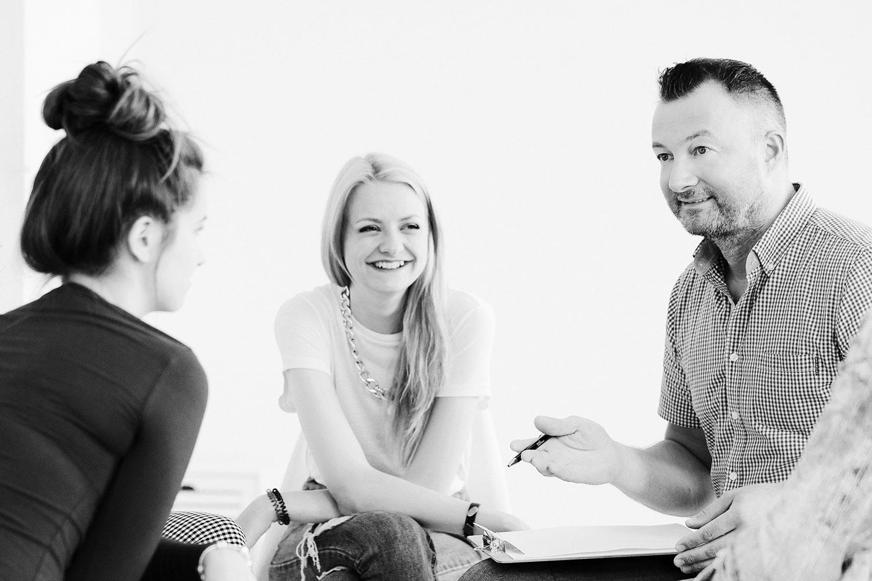 Drei Personen sitzen im Kreis und diskutieren