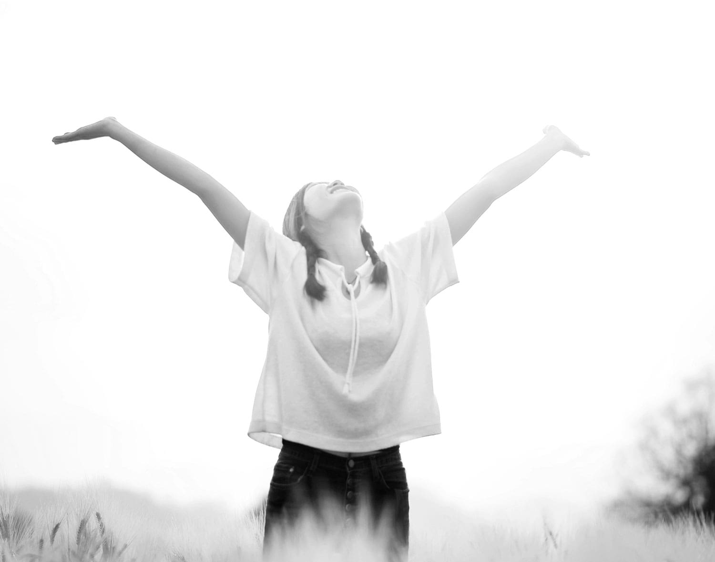 Frau streckt beide Arme in die Höhe und lacht in den Himmel